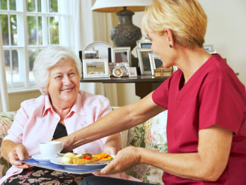 caregiver serving food to old woman